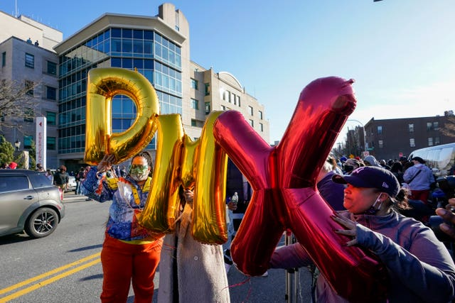 Fans hold up DMX balloons during a prayer vigil outside of White Plains Hospital in White Plains, New York