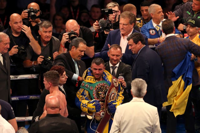 Vasyl Lomachenko (centre) added the WBC lightweight title to his WBA and WBO belts by beating Britain's Luke Campbell on points in London
