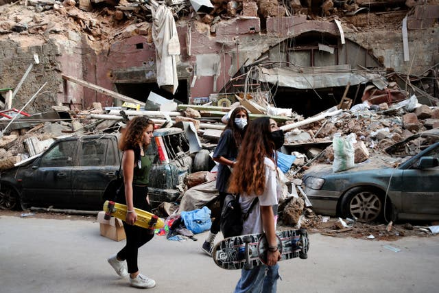 Women walk past destroyed cars in a neighbourhood near the scene of Tuesday's explosion that hit the seaport of Beirut, Lebanon