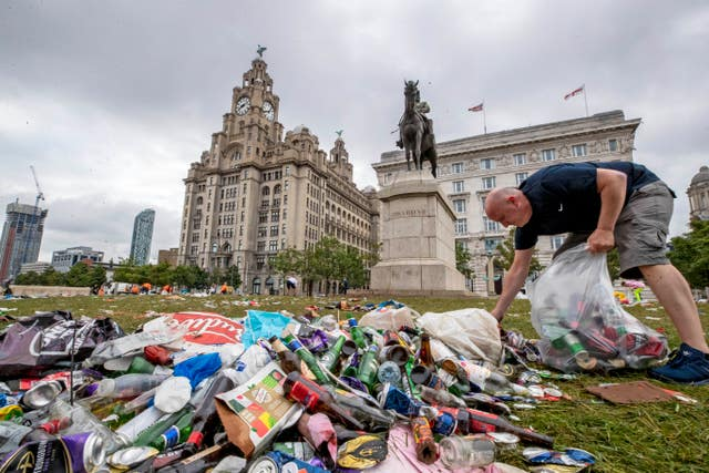 Workmen clear up rubbish left outside the Liver Building