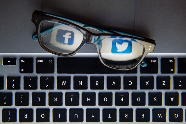 The logos of social network sites Facebook and Twitter reflected in a pair of glasses (Dominic Lipinski/PA)
