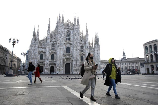 Tourists outside the Duomo Gothic cathedral in Milan, Italy