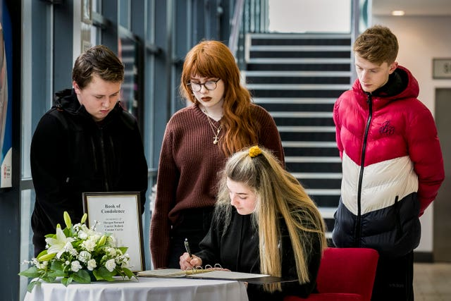 Youngsters sign a book of condolence in Cookstown for the families of three teenagers who died outside the Greenvale Hotel