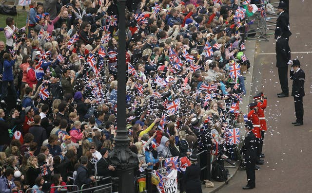 Confetti is thrown by the crowd gathered outside Buckingham Palace for the wedding of the Duke and Duchess of Cambridge at Westminster Abbey (David Bebber/PA)