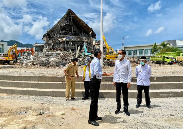 Indonesian President Joko Widodo, second right, talks to an official as as he inspects an earthquake-damaged government building