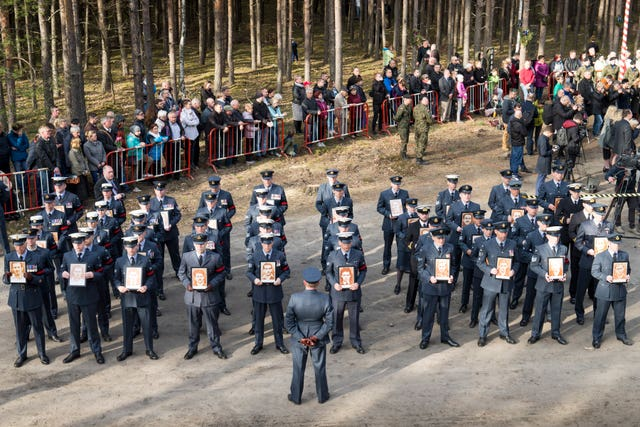 Air force personnel parade at the former site of Stalag Luft III in Zagan, Poland, during a remembrance service to commemorate the 75th anniversary of the Great Escape