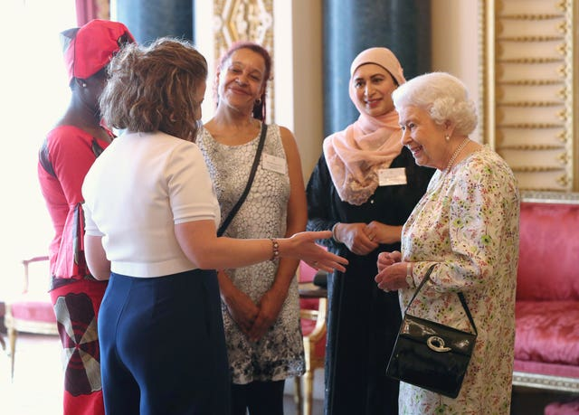 Queen Elizabeth II greets (left to right) Valentine Nkoyo, Anna Dyson, Rachael Cox, and Nighat Khan at the reception (Jonathan Brady/PA)