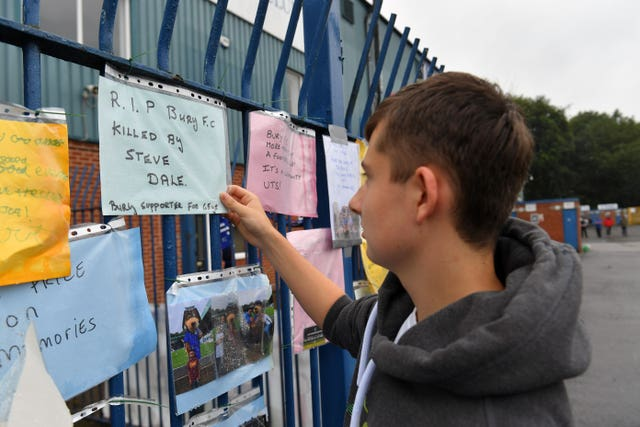 Messages from supporters are placed on a fence outside Gigg Lane
