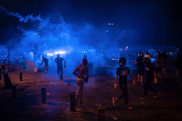 Protesters run from tear gas fired by police forces during an anti-government protest