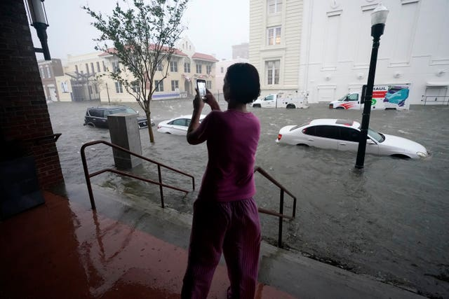A woman pictures the flooding