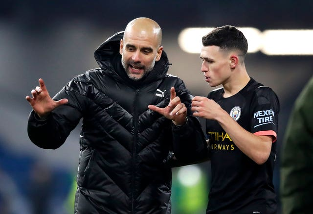 Manchester City manager Pep Guardiola celebrates the victory with Phil Foden