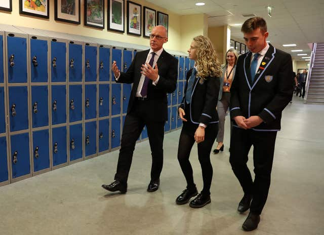 John Swinney with pupils Paige Dunlop and Michael Irwin at Clydebank High School (Andrew Milligan/PA)