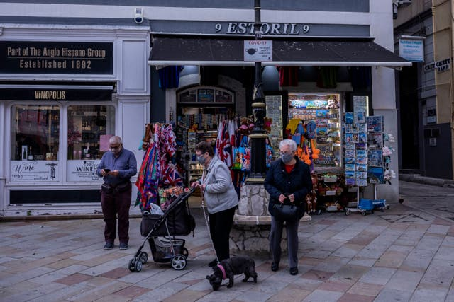 Two elderly women walk past a souvenir shop in Gibraltar