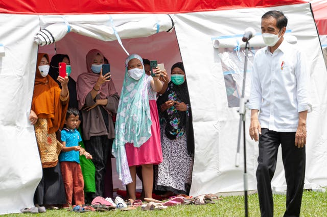 People displaced by the recent earthquake take photos of President Joko Widodo