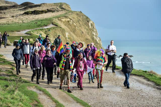 Natalia Spencer joined by dozens of supporters as she finishes her 6,000 mile walk around the coast of Britain (Ben Birchall/PA)