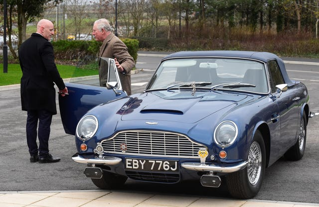 The Prince of Wales with his Aston Martin DB6 as he arrives for a visit to the Aston Martin Lagonda factory in Barry (Rebecca Naden/PA).