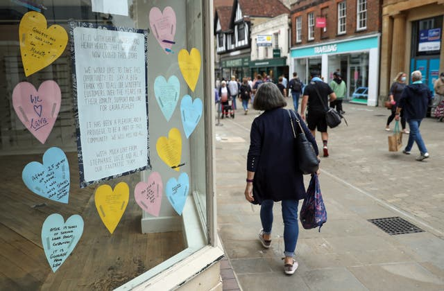 People walk past a closed down Laura Ashley shop, with messages from staff and customers in the shop window, on the high street in Winchester, Hampshire, some six months on from the evening of March 23 when Prime Minister Boris Johnson announced nationwide restrictions