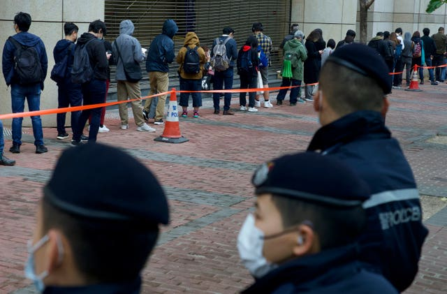 Police officers stand guard as supporters queue up for a court hearing in Hong Kong