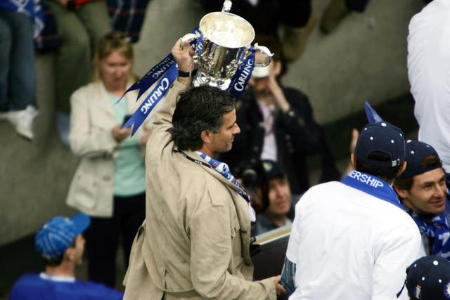 Jose Mourinho holds the League Cup trophy aloft