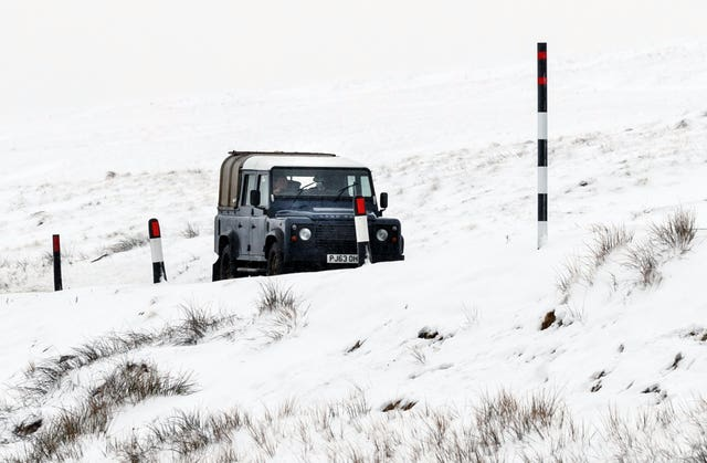 A car navigates the Buttertubs Pass in snowy conditions, near Hawes in North Yorkshire