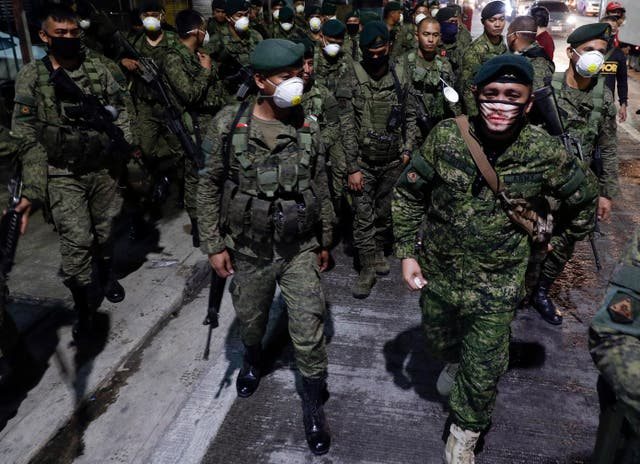 Filipino troops wearing protective masks arrive in Manila to start sealing the capital from most domestic travellers