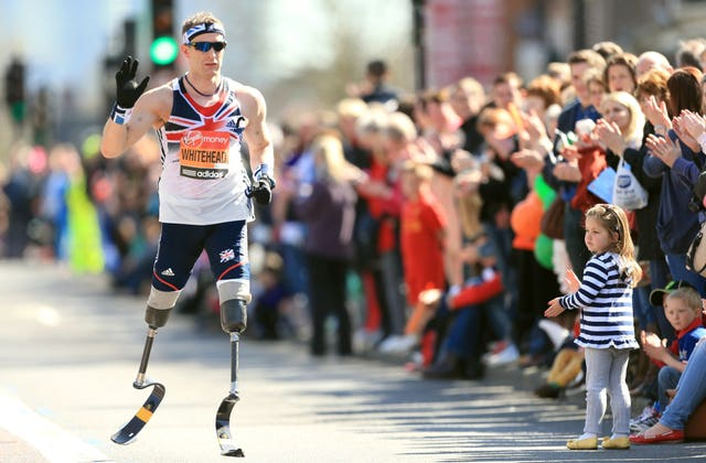 Great Britain's paralympic gold medallist Richard Whitehead waves to crowds during the 2013 London Marathon. Whitehead, who set a new world record when winning gold in the 200m in the T42 category at London 2012 the previous year