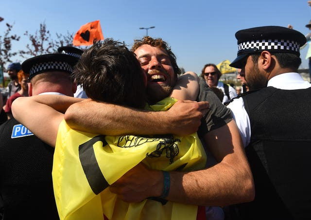 Extinction Rebellion demonstrators hug across a police cordon on Waterloo Bridge (Victoria Jones/PA)