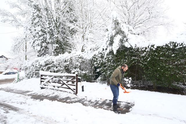 Man clears snow from driveway