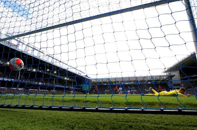 Jordan Pickford lies prone on the ground as Bruno Fernandes' shot hits the net