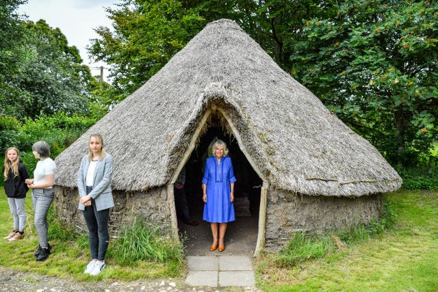 The Duchess of Cornwall peers out from a traditional straw hut during a visit to the Youth Action Wiltshire Oxenwood Outdoor Activity Centre near Marlborough, Wiltshire