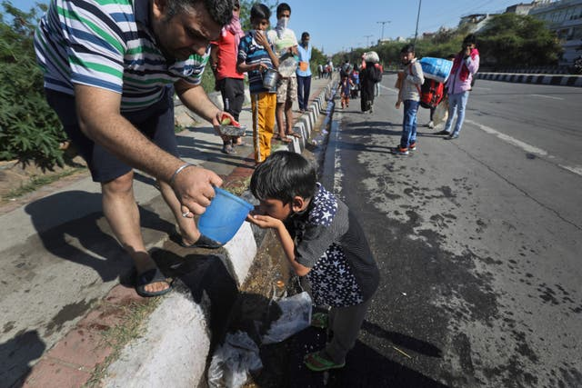 A resident offers water to a child of a migrant daily wage labourer as he and his family make the journey to their village following a lockdown amid concern over the spread of coronavirus in New Delhi, India