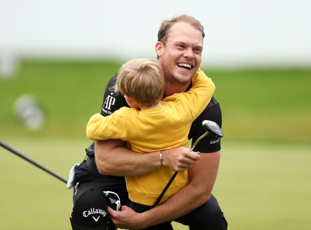 Danny Willett gets a hug from son Zachariah James after winning