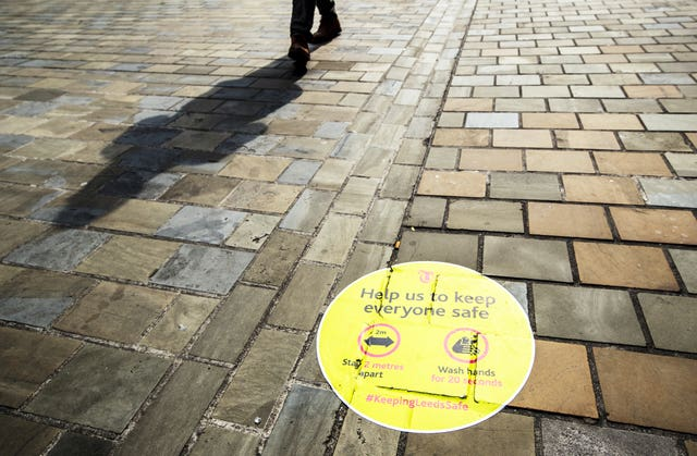 A person casts a shadow walking past a social distancing information sign painted on the pavement in Leeds city centre, some six months on from the evening of March 23, when Prime Minister Boris Johnson announced nationwide restrictions