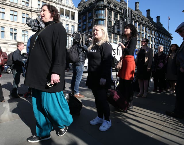 Derry Girls cast members Siobhan McSweeney, left, and Nicola Coughlan join women impacted by Northern Ireland's strict abortion laws who are carrying suitcases, symbolising the women who travel from Northern Ireland for abortions, across Westminster Bridge demanding legislative change