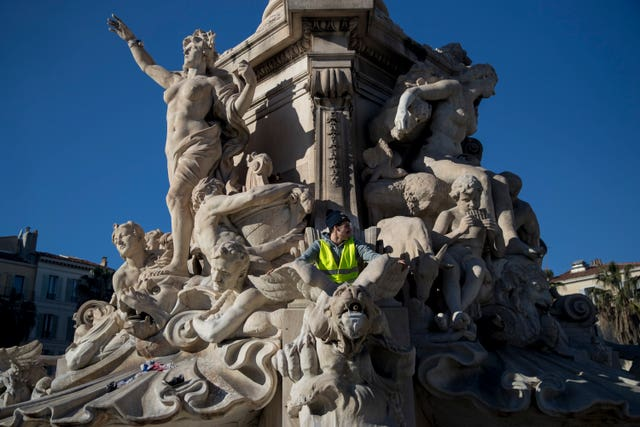 A protester in a yellow vest sits on top of a statue during a demonstration in Marseille, southern France