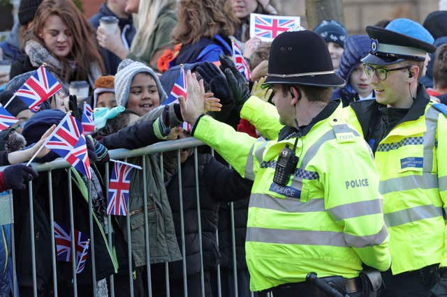 Police officers high-five children as they await the arrival of the Duke and Duchess of Cambridge in Coventry