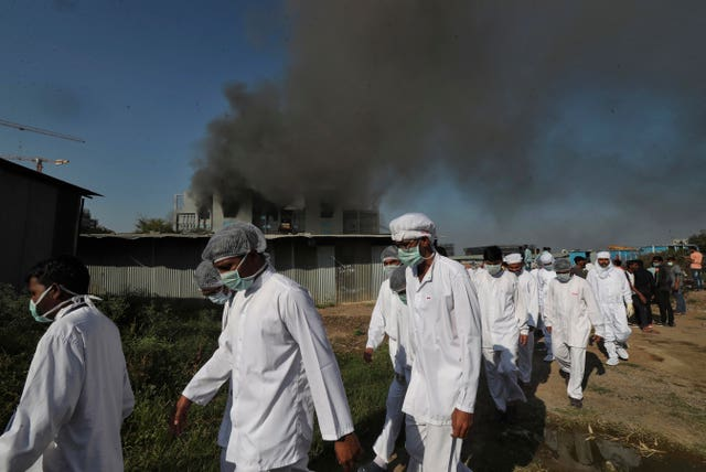 Employees leave as smoke rises from a fire at the Serum Institute of India, the world's largest vaccine maker in Pune