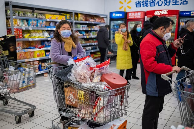 Shoppers wear face masks as they line up at a grocery store in Wuhan in central China's Hubei Province