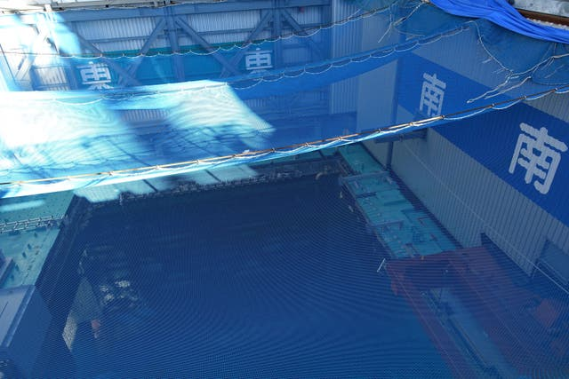 A cooling pool where a total of mostly used 566 sets of fuel rods are stored underwater and covered by a protective net