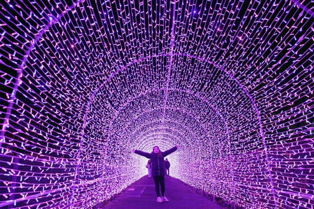 Girl stands in light tunnel