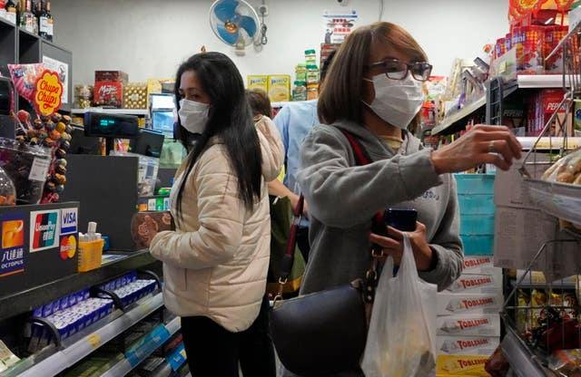 Shoppers buy goods at a convenience store in Hong Kong