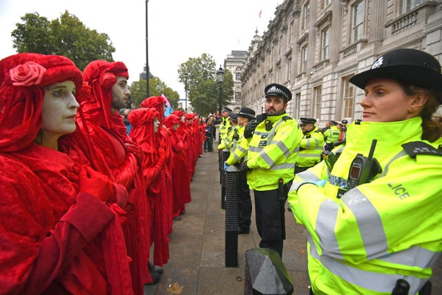 Protesters, dubbed the Red Rebels, outside the Cabinet Office on Whitehall, during an Extinction Rebellion (XR) protest in Westminster, London (Victoria Jones/PA)