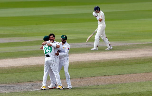 Dom Sibley, right, leaves the field as Pakistan celebrate taking his wicket