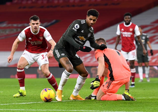 Manchester United's Marcus Rashford battles for the ball with Arsenal's Granit Xhaka and goalkeeper Bernd Leno