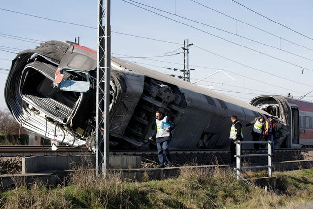 Police inspect an overturned carriage of a high-speed train after it derailed in the countryside near the town of Lodi, northern Italy