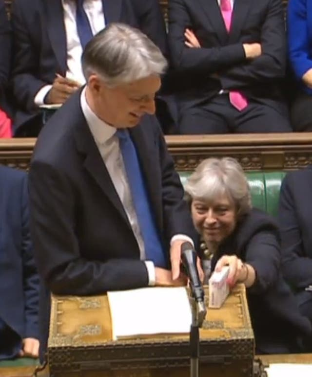 Prime Minister Theresa May passes Chancellor Philip Hammond a box of Strepsils during the autumn Budget (PA)