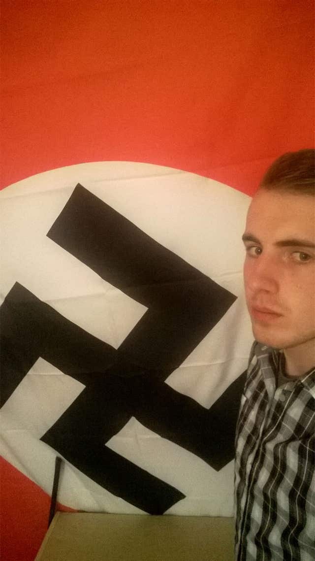 Ethan Stables posing next to a Nazi flag at his flat in Barrow (Greater Manchester Police/PA)