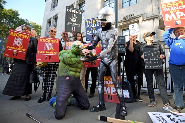 Protesters dressed as the Incredible Hulk and Robocop outside the Supreme Court