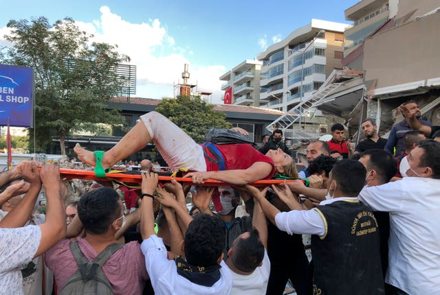 Rescue workers and local people carry a wounded person