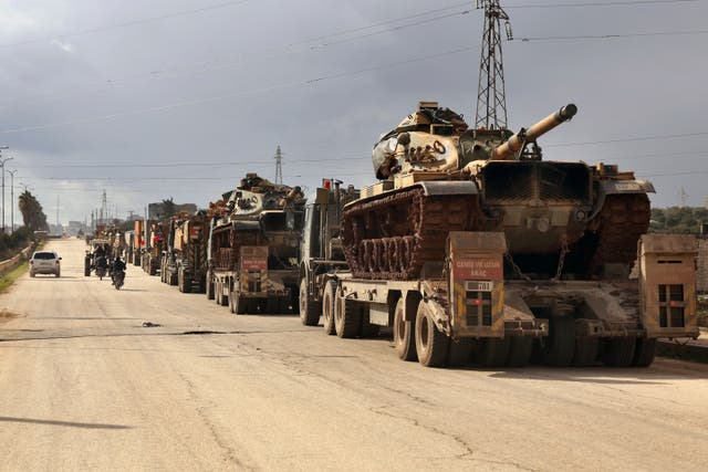 A Turkish military convoy drives through the village of Binnish in Idlib province, Syria